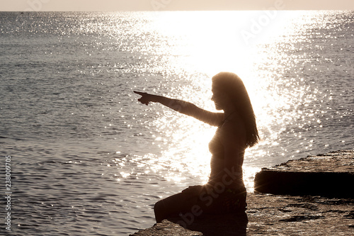 Fototapeta Woman`s silhouette doing yoga exercises. Woman making yoga poses on the sunset. Young girl relaxing on the sea shore on the sunrise. Morning warming up. Unrecognizable woman on the ocean coast.