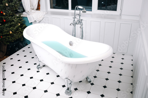 White bath in the luxury interior near Christmas tree