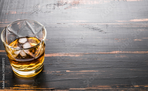 glass of whiskey on dark wooden tabletop
