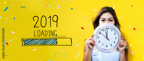 Loading new year 2019 with young woman holding a clock showing nearly 12 - 238030500