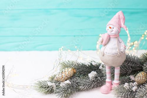 Mała dekoracyjna bałwan zabawka, jedlinowa świerczyna i czarodziejscy światła na jaskrawym drewnianym tle ,.