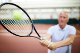 Blurred tennis player hitting ball with racket while playing on large stadium or court