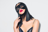 Beauty sexy brunette woman portrait. Girl wearing carnival black feather mask. Black hair, red lips, holiday makeup - 238048740
