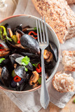 Spicy mussels served with cold white wine - 238048915