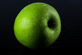 ripe green apple on black background