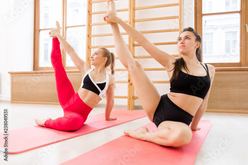 Two young active females in sportswear raising and stretching right legs while exercising on mats