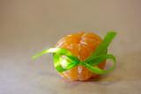 Peeled mandarin with green ribbon tied as bow