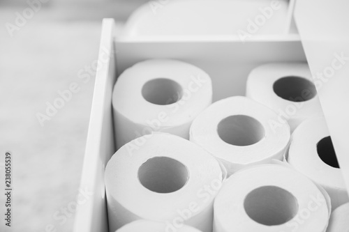 Open cabinet drawer with toilet paper rolls in bathroom