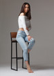 stylish asian female sitting on chair isolated on gray background