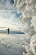 Natural ice formations at sunset, cross-country skier silhouette in distance, selective focus.