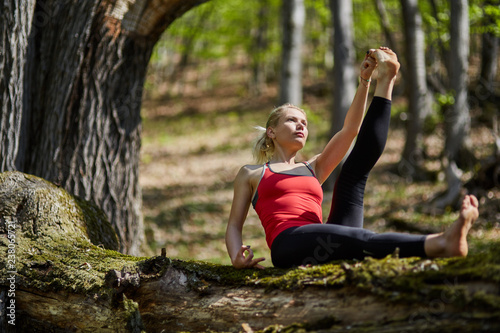 Naklejka Young woman doing yoga in a forest