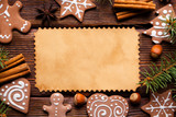 Blank paper card, gingerbread Christmas cookies and spices on wooden background