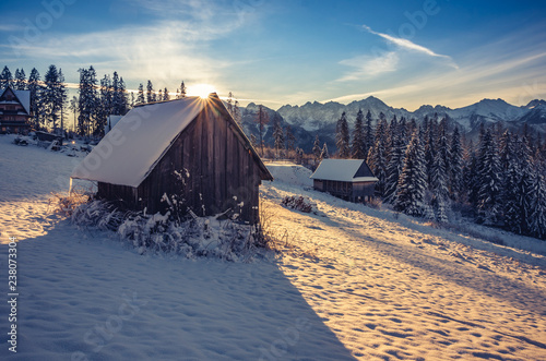 Wooden mountain hut in the morning, snowy winter