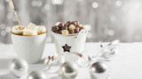 A cup of cocoa with marshmallows and corn balls in the New Year