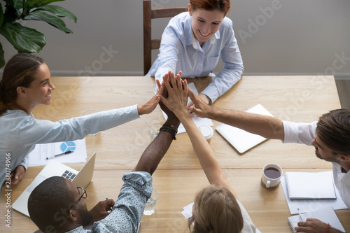 Leinwanddruck Bild Diverse millennial partners company staff feels happy reached business goal giving high five stack palms together sitting at office desk in boardroom in conference, top above view. Team spirit concept
