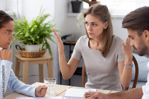 Leinwanddruck Bild Dissatisfied team leader talking with colleagues discussing failure in work,  coworkers having different opinion sitting together in office arguing disputing blond colleague insists on her point o