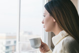 Young beautiful woman enjoying morning coffee by the window - 238085957