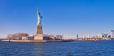 Fototapeta New York - Vista desde el rio Hudson, al atardecer, de la estatua de la libertadla isla de la libertad y el horizonte de Manhattan , donde numerosos turistas, van a visitarla cada dia,desde Manhattan. © Helena GH