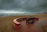 un banc face à une plage et une mer agitée avec de gros nuages menaçant  © Olivier Tabary