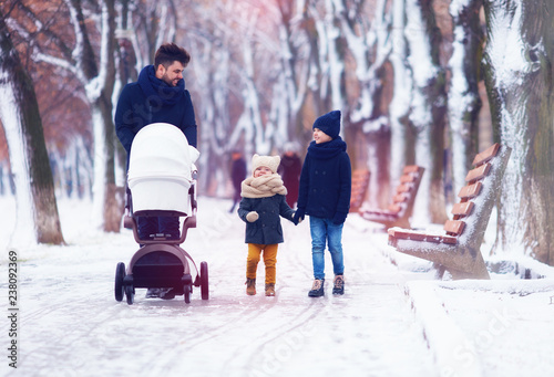 Leinwanddruck Bild happy family, father with kids walking on the winter street