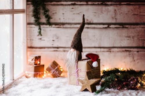 Kleiner Wichtel sitzt auf Geschenken vor einem Fenster und wartet mit seiner weihnachtsmütze auf Heiligabend - Vintage, Weihnachten, Winter, süß - 238094162