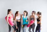 Group of young sporty woman with yoga mats standing at white wall.