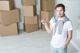 Man in a new house holds the keys on the background of boxes. - 238102560