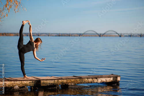 Fototapeta Young woman practicing yoga exercise at quiet wooden pier with city background. Sport and recreation in city rush