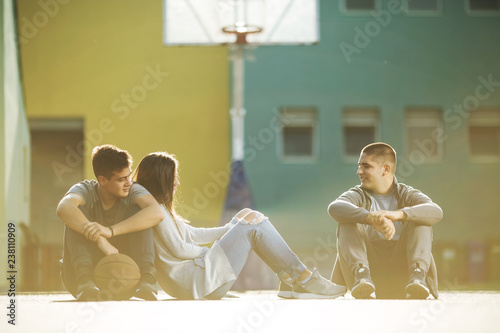Three teenagers sitting on basketball court