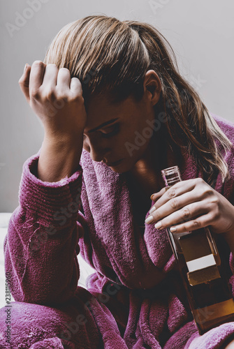 Addicted and depressed women sitting in bedroom with glass of alcohol in hand.