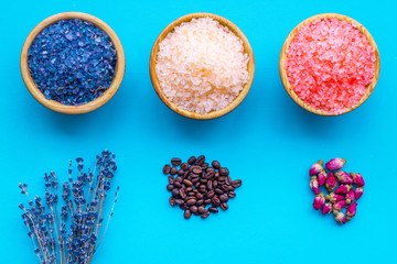 Aromas of bath salt. Coffee, rose, lavender near bowls with colorful bath salt on blue background top view © 9dreamstudio