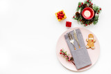 Christmas dinner decoration with gift box, plate and fir tree white table background top view mock-up
