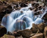 Mountain stream cascade falls over rocks