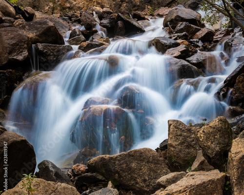Mountain stream cascade falls over rocks