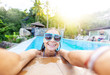 Leinwandbild Motiv Beautiful young girl in a swimming pool overlooking the tropical jungle, traveling and vacations on a tropical paradise island, doing selfie