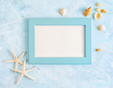 Flat lay top view Summer vacation mockup: photo frame, seashells and white starfish on blue background. Travel, beach concept. Space for text or lettering
