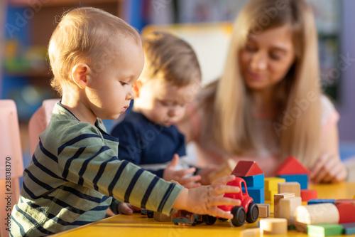 Leinwanddruck Bild Preschool teacher and cute kids boys playing in kindergarten