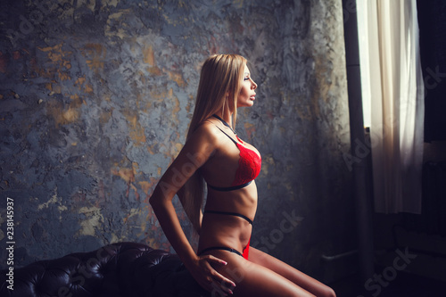 gorgeous and sensual woman in red lingerie in a dark room - 238145937