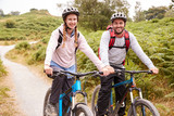 Young adult couple sitting on mountain bikes in a country lane during a camping holiday, close up