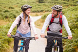 Young adult couple riding mountain bikes in a country lane, looking each other, close up