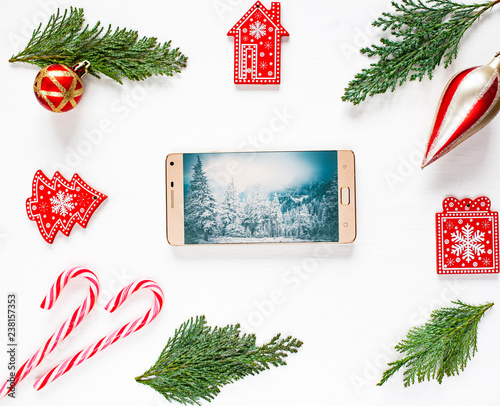 christmas composition with gifts, fir tree branches, red decorations, smartphone and candy cane on white background. Christmas, winter, new year concept. Flat lay, top view, copy space