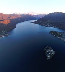 Aerial view of Lake Orta (Piedmont, Italy) with the San Giulio island at dawn on a sunny winter day.