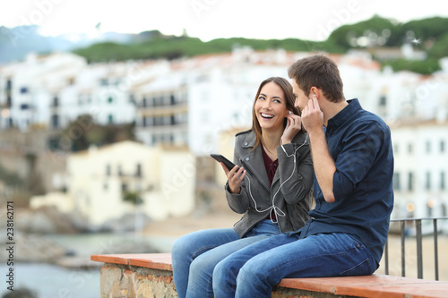 Leinwanddruck Bild Happy couple sharing music on a ledge