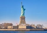 Fototapeta New York - Vista desde el rio Hudson, al atardecer, de la estatua de la libertad y su isla, donde numerosos turistas, van a visitarla cada dia,desde Manhattan. © Helena GH