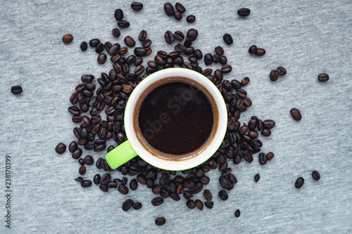 cup of coffee with beans on grey background