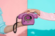 Leinwanddruck Bild - cropped view of man and woman holding purple vintage telephone on pink and blue background