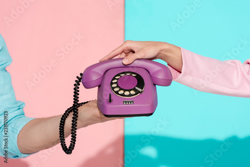 Leinwanddruck Bild cropped view of man and woman holding purple vintage telephone on pink and blue background