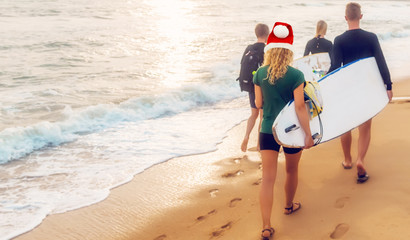 bikini girl in Santa Claus red hat surfers running