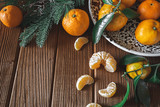 Fresh delicious mandarin oranges fruit or tangerines with green leaves in a bowl on wooden table