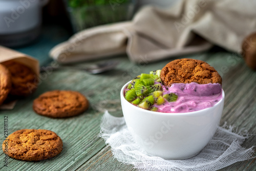Foto Murales Healthy breakfast. Blueberry yogurt, biscuits and kiwi on a wooden table. Bright photo.